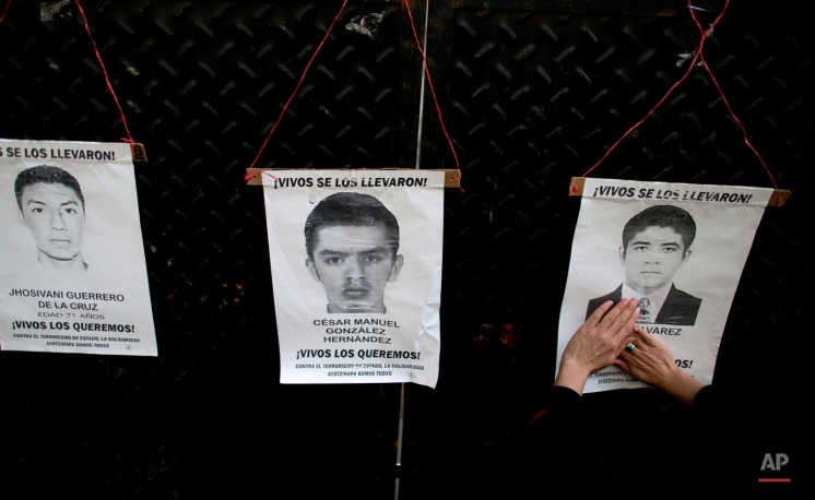 A woman places a portrait of one of Mexico's 43 missing students on a fence outside the Mexican embassy in Buenos Aires, Argentina, Friday, Sept. 25, 2015, one day before the one year anniversary of the attack on Ayotzinapa students'. According to an independent group of experts, the disappearances of 43 students and the killings of six others were the result of a long, coordinated attack against students from the Raul Isidro Burgos Rural Normal School of Ayotzinapa in Mexico. (AP Photo/Natacha Pisarenko)