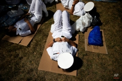 Members of the U.S. Naval Academy rest on the ground while waiting for Pope Francis to arrive for a Mass, Wednesday, Sept. 23, 2015, outside the Basilica of the National Shrine of the Immaculate Conception in Washington. (AP Photo/David Goldman)