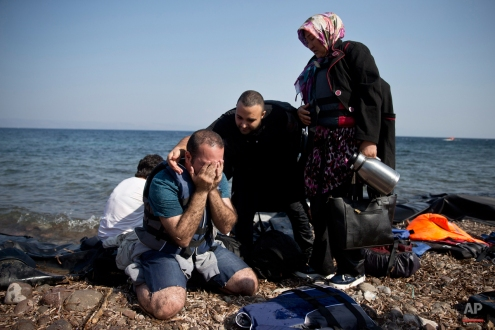 Yshar, left, a 36 year old musician from Iran reacts on the shores of the Greek island of Lesbos after crossing with others the Aegean Sea from Turkey on a inflatable dinghy, Monday, Sept. 21, 2015. Greece's coast guard was searching Sunday for 26 migrants missing off the coast of the eastern Aegean island of Lesbos after the boat they were traveling in sank. (AP Photo/Petros Giannakouris)