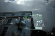 Migrants are reflected in the window of a car as volunteers distribute clothes at Victoria square, where many stay temporarily before trying to continue their trip to more prosperous northern European countries, in Athens on Wednesday, Sept. 23, 2015. The 28-nation EU took a modest step toward dealing with the issue by agreeing to relocate 120,000 asylum-seekers to ease the strain on Greece and Italy, which are on the front line of the migrant flood. (AP Photo/Fotis Plegas G.)