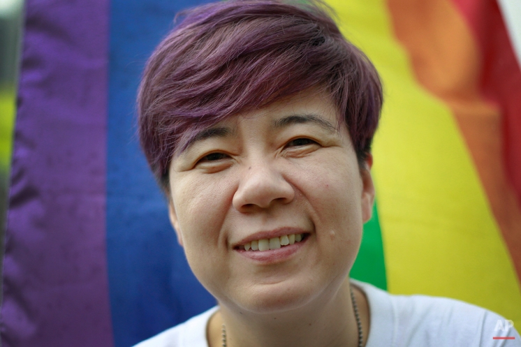 """In this Aug. 20, 2015, photo, Han Chae-yoon poses for a photograph in front of Seoul City Hall, the site of this year's gay pride parade. Han, who has helped organize the Korea Queer Culture Festival, said she didn't question her sexual orientation until after she reached her mid-20s, the age when it is socially expected to get married. """"If I were to get married, I wanted to live with someone that I truly love, and that had always been a woman,"""" she said. (AP Photo/Julie Yoon)"""