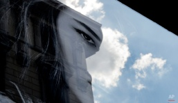 Clouds are reflected in the window of a clothes shop displaying a poster of a model, in Milan, Italy, Friday, Sept. 18, 2015. (AP Photo/Luca Bruno)