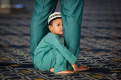 A young Malaysian Muslim child peeks while his father prays during the Islamic holiday of Eid al-Adha at a mosque in Shah Alam outside Kuala Lumpur, Malaysia on Thursday, Sept. 24, 2015. Muslims in the country start celebrating Eid al-Adha, or the Feast of the Sacrifice, which honors the prophet Abraham for his willingness to sacrifice his son Ishmael on the order of God who was testing his faith. (AP Photo/Joshua Paul)