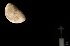 The moon rises over a cross at the GSP stadium, in capital Nicosia, Cyprus, Thursday, Sept. 3, 2015. (AP Photo/Petros Karadjias)