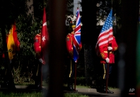 Romanian honor guard soldiers hold NATO member states flags during the ceremony of inauguration of a NATO force integration unit in Bucharest, Romania. The NATO force integration unit in Bucharest is one of six small headquarters manned by some 40 staff each, that opened this month in Bulgaria, Estonia, Latvia, Poland, Lithuania and Romania, as part of the alliance's biggest reinforcement of collective defense since the end of the Cold War. (AP Photo/Vadim Ghirda)