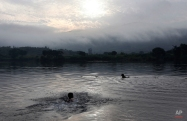 Two boys swim in the Paung Laung River early Wednesday morning, Sept 23, 2015, in Naypyitaw, Myanmar. (AP Photo/Aung Shine Oo)