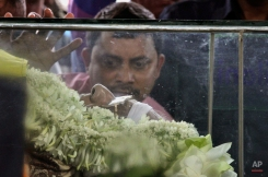 The body of Jagmohan Dalmiya, Board of Control for Cricket in India (BCCI) president and former International Cricket Council chief, is placed in a glass casket during his funeral in Kolkata, India, Monday, Sept. 21, 2015. Dalmiya, the top sports administrator credited with making India a major financial power in cricket, was admitted to a hospital in Kolkata on Thursday following a cardiac arrest. He died Sunday, Sept. 20, 2015, at the age of 75. (AP Photo/Bikas Das)