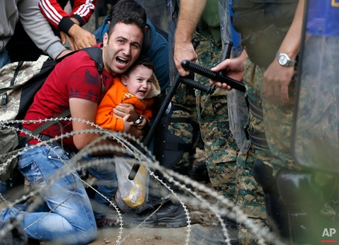 A migrant man and a boy react as they are stuck between Macedonian riot police officers and migrants during a clash near the border train station of Idomeni, northern Greece, as they wait to be allowed by the Macedonian police to cross the border from Greece to Macedonia, Friday, Aug. 21, 2015. (AP Photo/Darko Vojinovic)