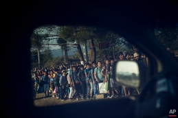Migrants are seen through the window of a police car at the Greek-Macedonian border, as they wait to be allowed by Macedonian police to cross the border, Idomeni, northern Greece, Thursday, Aug. 27, 2015. (AP Photo/Santi Palacios)