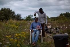 A Sudanese migrant gets a haircut at a camp set near Calais, northern France. Aug. 6, 2015. (AP Photo/Emilio Morenatti)