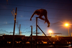 A migrant jumps a fence as he attempts to access the Channel Tunnel in Calais, northern France, Wednesday, Aug. 5, 2015. (AP Photo/Emilio Morenatti)