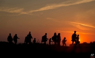 Refugees from the Middle East are silhouetted against the setting sun as they walk on railway tracks from Serbia, in Roszke, Hungary, Sunday, Aug. 30, 2015. (AP Photo/Darko Bandic)