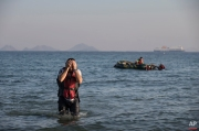 A Syrian migrant arrives after crossing from Turkey by a rubber boat, seen in the background, in the southeastern island of Kos, Greece, Monday, Aug. 17, 2015. (AP Photo/Alexander Zemlianichenko)