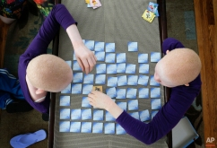Pendo Noni, left, and Kabula Masanja play a memory card game in New York on Tuesday, July 28, 2015. Pendo and Kabula were attacked and dismembered in the belief that their body parts will bring wealth. (AP Photo/Julie Jacobson)