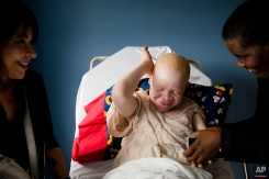 Emmanuel Rutema, 13, of Tanzania laughs with Elissa Montanti, left, founder and director of the Global Medical Relief Fund, and interpreter Ester Rwela ahead of his surgery at the Shriners Hospital for Children in Philadelphia on Tuesday, June 30, 2015. (AP Photo/Matt Rourke)