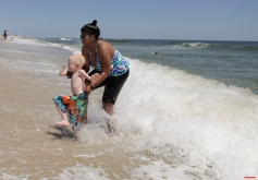 Global Medical Relief Fund assistant Monica Watson, right, helps Baraka Lusambo, 5, dart away from an approaching wave in Long Beach Island, N.J. on Wednesday, July 22, 2015. Baraka was attacked and dismembered in the belief that their body parts will bring wealth. (AP Photo/Julie Jacobson)