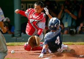Lewisberry, Pa.'s Braden Kolmansberger (4) scores ahead of the throw to Japan's Raito Sugimoto on a single by Chayton Krauss during the first inning of the Little League World Series Championship baseball game in South Williamsport, Pa., Sunday, Aug. 30, 2015. (AP Photo/Gene J. Puskar)