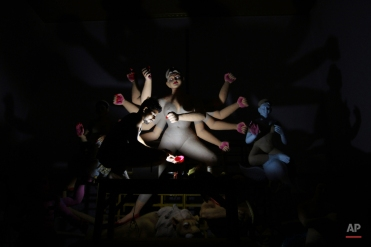 An artist colors a clay idol of Hindu goddess Durga in emergency torch light during a power cut at a worshipersí venue ahead of the Durga Puja festival, in the eastern Indian city Bhubaneswar, India, Monday, Oct. 12, 2015. he festival, to be celebrated from Oct. 19 to 22, commemorates the slaying of a demon king by lion-riding, ten armed goddess Durga, marking the triumph of good over evil. (AP Photo/Biswaranjan Rout)