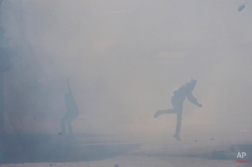 Kashmiri protesters throw rock and bricks at Indian policemen amid tear gas smoke during a protest in Srinagar, Indian controlled Kashmir, Friday, Oct. 2, 2015. Police fired teargas and rubber bullets to disperse hundreds of Kashmiris who gathered after Friday afternoon prayers to protest against the arrest of separatist leaders and civilians. They were also protesting against the ban on the sale of beef across the state. (AP Photo/Dar Yasin)