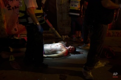 A body of an attacker lies on the street after he was shot and killed when he stabbed an Israeli woman in Jerusalem Wednesday, Oct. 14, 2015. Police spokeswoman Luba Samri said the attacker stabbed the 70-year-old woman Wednesday before he was shot by forces at the scene. (AP Photo/Oren Ziv)