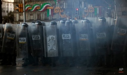 Police enter the Zocalo, or main plaza, at the end of a march marking the anniversary of the Tlatelolco Massacre in Mexico City, Friday, Oct. 2, 2015. Mexico commemorated the 47th anniversary of the massacre where students and civilians where killed by the military and police on October 2, 1968. The events are considered part of the Mexican Dirty War when the government used its forces to suppress political opposition. The massacre occurred 10 days before the opening of the 1968 Summer Olympics in Mexico City. (AP Photo/Marco Ugarte)