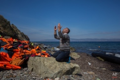A refugee prays shortly after he and other migrants arrived on a dinghy from the Turkish coast to the northeastern Greek island of Lesbos, Thursday, Oct. 1, 2015 The International Organization for Migration says a record number of people have crossed the Mediterranean into Europe this year, now topping a half a million as some 388,000 have entered via Greece.(AP Photo/Santi Palacios)