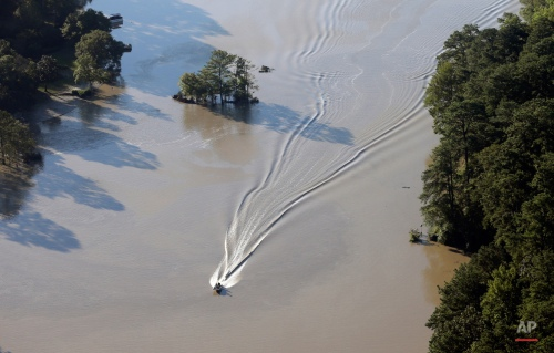 A boater pilots a boat down a lake in Columbia, S.C., Tuesday, Oct. 6, 2015. Despite an improving forecast, it will still take weeks for the state to return to normal after being pummeled by a historic rainstorm. (AP Photo/Chuck Burton)