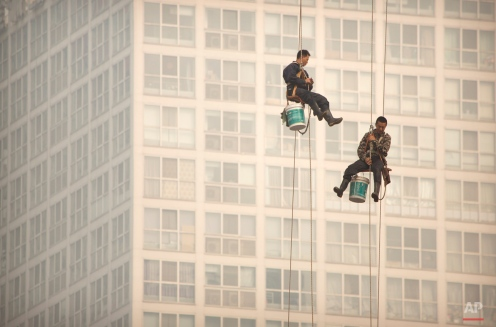 Window washers use cables to lower themselves from a skyscraper while working on a polluted day in Beijing, Tuesday, Oct. 6, 2015. Air quality readings in the city on Tuesday were at levels considered hazardous by international measuring standards. (AP Photo/Mark Schiefelbein)