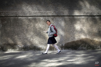 A North Korean school girl looks up from reading her book while walking through a residential area Wednesday, Oct. 14, 2015 in Pyongyang, North Korea. (AP Photo/Wong Maye-E)