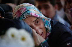 """A relative of Vahdettin Ozkan, 52, one of the victims killed in Ankara's Saturday's bombing attacks, cries over his coffin during the funeral in Istanbul, Monday, Oct. 12, 2015. Turkish investigators are close to identifying one of the suicide bombers in Turkey's deadliest attacks in years, Prime Minister Ahmet Davutoglu said Monday, adding that the Islamic State group was the """"Number one priority"""" of the investigation. (AP Photo/Lefteris Pitarakis)"""