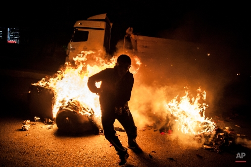 A leftist protester runs from a barricade after protesters set it on fire, during minor clashes with Turkish security forces following a protest against Saturday's Ankara bombing attacks, in Istanbul's Gazi district, Monday, Oct. 12, 2015. Turkish investigators were close to identifying one of the suicide bombers in Turkey's deadliest attacks in years, Prime Minister Ahmet Davutoglu said Monday. (AP Photo/Cagdas Erdogan)