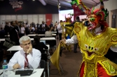 """A man attending the annual meetings by the World Bank Group and IMF watches a man perform a traditional dance from Puno, Peru called """"La Diablada"""" inside the venue's dining area in Lima, Peru, Friday, Oct. 9, 2015. More than 60 percent of Peruvians workers are in the informal economy, according to U.N. figures, spending on health care and education are below regional averages and most government revenues come not from income tax but rather taxes on sales and consumption, putting the burden disproportionately on the poor in the region with the world's most unequal wealth distribution. (AP Photo/Rodrigo Abd)"""