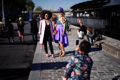 Fashion lovers pose along the Seine river before the start of Indian designer Manish Arora's Spring-Summer 2016 ready-to-wear fashion collection, presented during the Paris Fashion Week in Paris, France, Thursday, Oct. 1, 2015. (AP Photo/Jerome Delay)