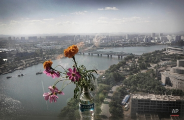 A vase of flowers, seen from a hotel window, overlooks the Taedong River, Monday, Oct. 12, 2015, in Pyongyang, North Korea. Pyongyang is the capital of North Korea. (AP Photo/Wong Maye-E)
