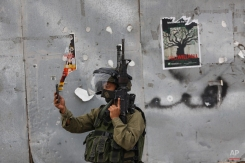 An Israeli soldier takes a photograph with his mobile phone during clashes with Palestinian demonstrators in the West Bank city of Bethlehem on Tuesday, Oct. 13, 2015. A pair of Palestinian men boarded a bus in Jerusalem and began shooting and stabbing passengers, while another assailant rammed a car into a bus station before stabbing bystanders, in near-simultaneous attacks Tuesday that escalated a monthlong wave of violence. (AP Photo/Nasser Shiyoukhi)