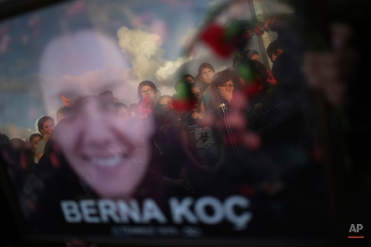 Mourners are reflected on a picture of Berna Koc, one of the victims of Saturday's Ankara bombing attacks, during a funeral in Izmir, Turkey, Monday, Oct. 12, 2015. Turkish investigators are close to identifying one of the suicide bombers in Turkey's deadliest attacks in years, Prime Minister Ahmet Davutoglu said Monday. (AP Photo/Emre Tazegul)