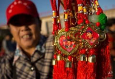 A seller holds medallions with the faces of Chinese President Xi Jinping, left, and former Chinese leader Mao Zedong at Tiananmen Square after a flag raising ceremony on National Day, the 66th anniversary of the founding of the People's Republic of China, in Beijing, Thursday, Oct. 1, 2015. (AP Photo/Mark Schiefelbein)