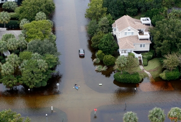 A kayaker makes her way through floodwaters on Sullivan's Island, S.C., Monday, Oct. 5, 2015. The Charleston and surrounding areas are still struggling with floodwaters due to a slow moving storm system. (AP Photo/Mic Smith)