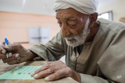 Esmail Ahmed , 82 years old, casts his ballot at a polling station during the final day of the first round of parliamentary election, in Fayoum , Egypt, Monday, Oct. 19, 2015. Egyptian authorities have given government workers a half-day off Monday in an attempt to bolster low turnout in the countryís parliamentary election. The government has not released turnout figures for voting on Sunday. (AP Photo/Eman Helal)