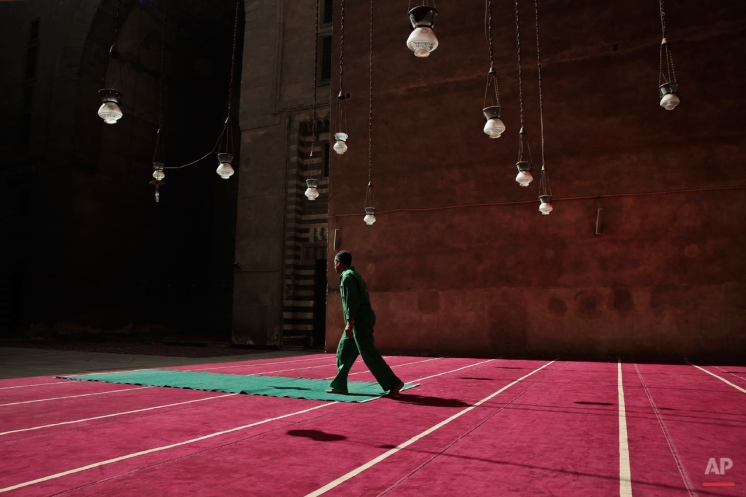 A worker cleans carpets at the Sultan Hassan Mosque and Madrassa in Cairo, Egypt, Wednesday, Oct. 7, 2015. The mosque and madrassa is considered to be a religious school for all four main Sunni 'madaheb' or schools of thought in Islam. The four consist of Hanafi, Maliki, Shafi'i, and Hanbali. (AP Photo/Nariman El-Mofty)