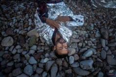 An exhausted man lays on a beach after his arrival on a dinghy from the Turkish coast to the northeastern Greek island of Lesbos, Monday, Oct. 19, 2015. More than 600,000 people, mostly Syrians, have reached Europe since the beginning of this year. (AP Photo/Santi Palacios)