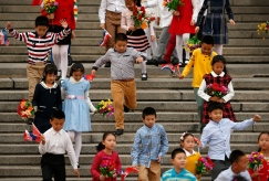 Schoolchildren carrying Chinese and Croatian flags arrive for a welcoming ceremony for Croatian President Kolinda Grabar-Kitarovic at the Great Hall of the People in Beijing, Wednesday, Oct. 14, 2015. (AP Photo/Mark Schiefelbein)