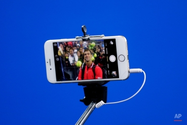 Novak Djokovic of Serbia takes a selfie with spectators after winning his men's singles quarterfinal match against John Isner of the United States in the China Open tennis tournament at the National Tennis Stadium in Beijing, Friday, Oct. 9, 2015. (AP Photo/Andy Wong)