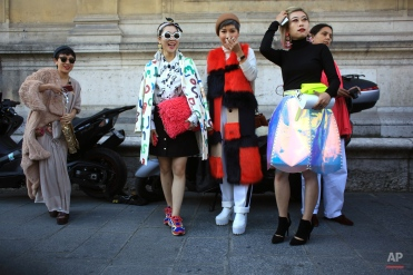 Fashion lovers pose for a picture outside Chalayan' Spring-Summer 2016 ready-to-wear fashion collection presented during the Paris Fashion Week, in Paris, France, Friday, Oct. 2, 2015. (AP Photo/Thibault Camus)