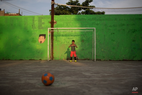 A boy prepares to defend a kick as he plays soccer at the Vidigal slum in Rio de Janeiro, Brazil, Friday, Oct. 2, 2015. Despite the recent wave of violence in other pacified favelas, Vidigal has been peaceful and is today a popular tourist spot. (AP Photo/Felipe Dana)