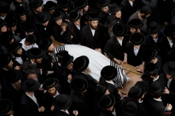 Ultra-Orthodox Jewish men gather around the body of Yeshayahu Kirshavski during his funeral in Jerusalem, Tuesday, Oct. 13, 2015. A pair of Palestinian men boarded a bus in Jerusalem and began shooting and stabbing passengers, while another assailant rammed a car into a bus station before stabbing bystanders, in near-simultaneous attacks Tuesday. (AP Photo/Oded Balilty)