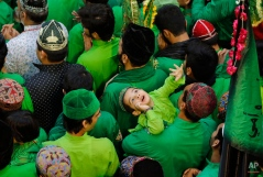 A child looks upwards as Indian Muslims pray during a procession of flags in memory of Abbas Alamdar, brother of Imam Hussein during the sacred Islamic month Muharram in Ajmer, India, Monday, Oct.19, 2015. (AP Photo/Deepak Sharma)