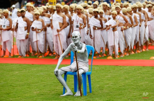 Shri Gopal, a Gandhian or follower of Gandhi's philosophy, sits dressed as Indiaís independence leader Mahatma Gandhi, as he is joined by school children also dressed as Gandhi in an attempt to create a Guinness record, during celebrations to mark Gandhiís birth anniversary in Bangalore, India, Friday, Oct. 2, 2015. 4605 children participated in the event to break the record of largest gathering of people dressed as Gandhi, according to organizers. (AP Photo/Aijaz Rahi)