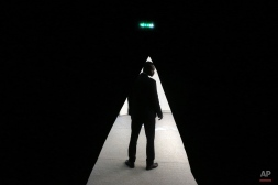 A usher stands backstage before the start of Issey Miyake's Spring-Summer 2016 ready-to-wear fashion collection presented during the Paris Fashion Week, in Paris, France, Friday, Oct. 2, 2015. (AP Photo/Thibault Camus)