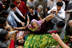 A Kashmiri Muslim woman wails near the body of a suspected rebel, during his funeral at Barhama, 40 kilometers (25 miles) south of Srinagar, Indian controlled Kashmir, Monday, Oct. 5, 2015. At least four Indian army soldiers and three suspected rebels were killed in three separated gun battles in Indian-controlled Kashmir, police said on Monday. (AP Photo/Mukhtar Khan)